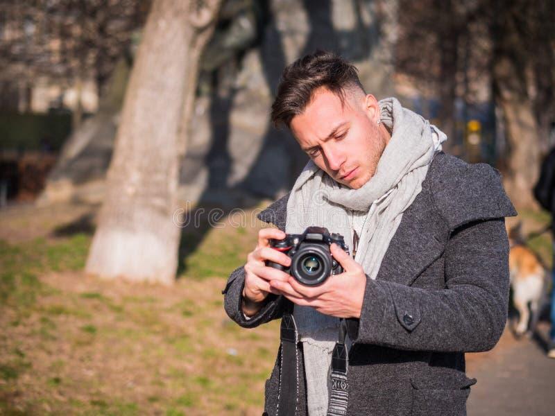 摄制录影镜头的英俊的年轻男性摄影师外面 免版税库存图片