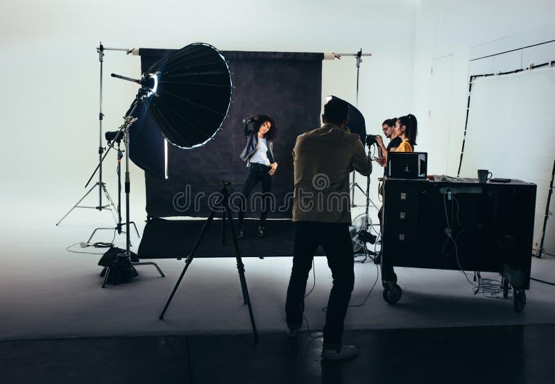 摄影师一个女性模型的射击照片与演播室一刹那光的 有他的队的摄影师在照片写真期间 免版税图库摄影