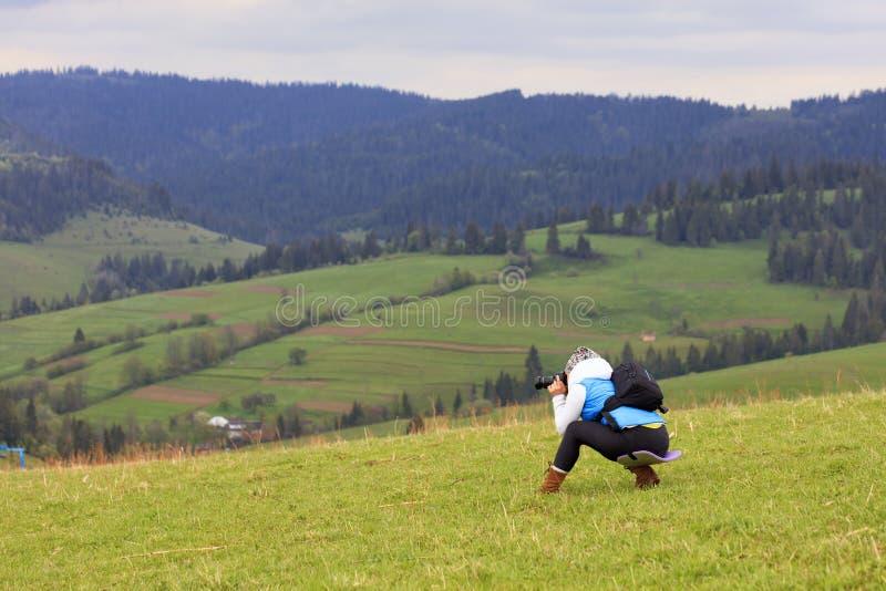 摄影师一半蹲下的射击喀尔巴阡山脉的倾斜的风景在一个新春天早晨 免版税库存图片