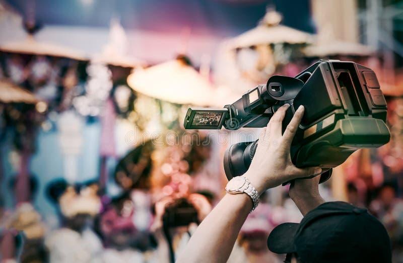 摄影师举在他的头上的摄象机,当摄制录影时 免版税库存照片