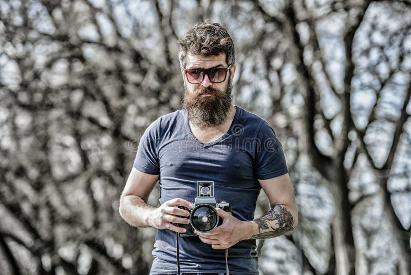 摄影师举行葡萄酒照相机 现代博客作者 美满的创作者 人有胡子的行家摄影师 摄影师与 库存照片