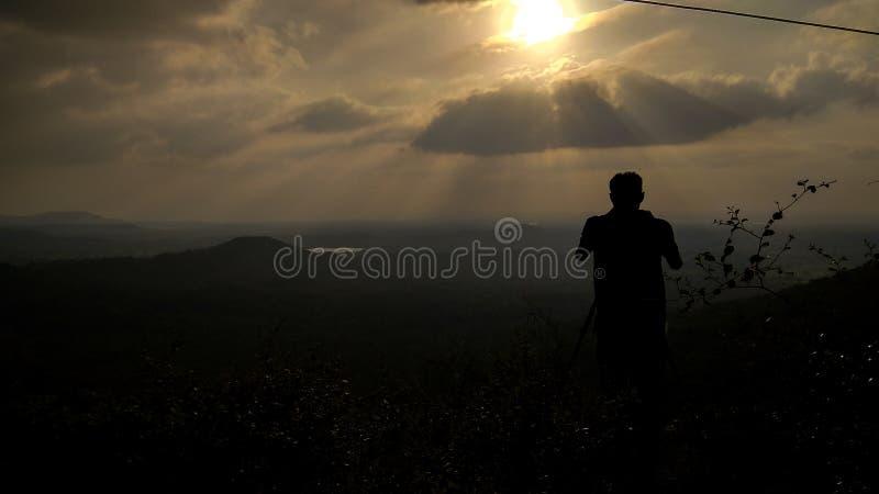 摄影师剪影和日落在山 库存照片