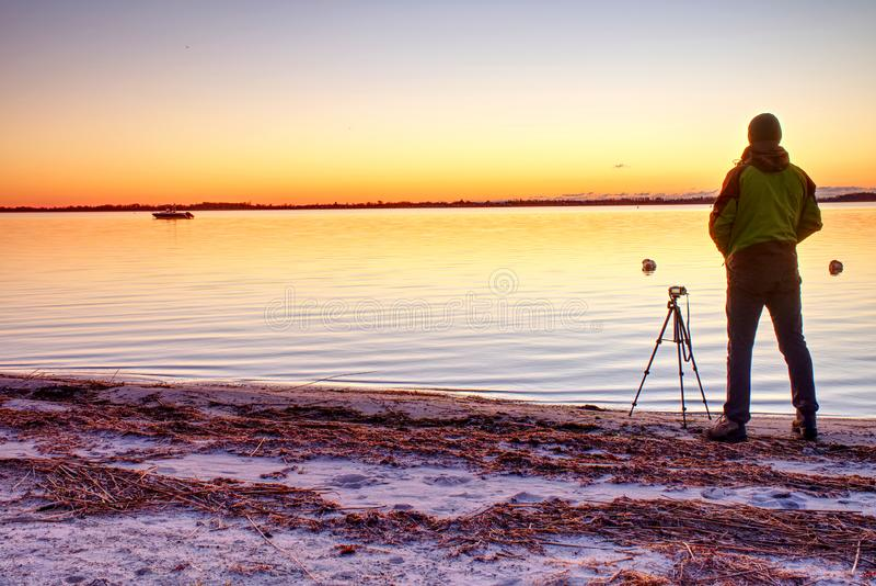 摄影师剪影拍秋天照片近海处与美丽的日落天空 免版税库存照片