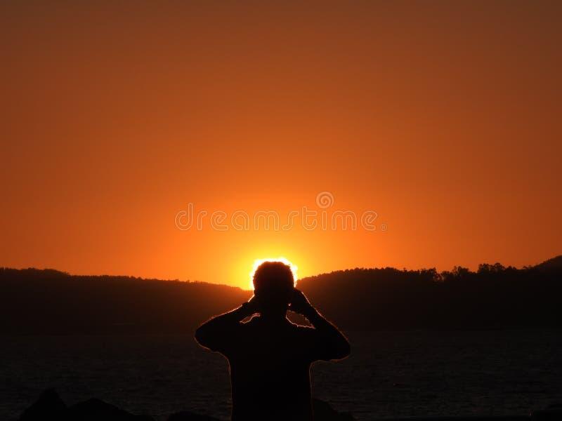 摄影师剪影 日落,人拍摄照片在阳光下,金黄,并且深色画他的剪影 免版税库存照片