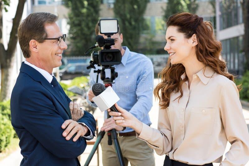 摄影师和女性新闻记者有话筒采访的专家的 免版税库存照片