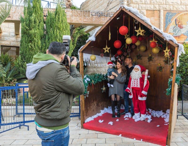 摄影师在拿撒勒市拍一个年轻家庭的照片与圣诞老人项目的在以色列 免版税库存照片