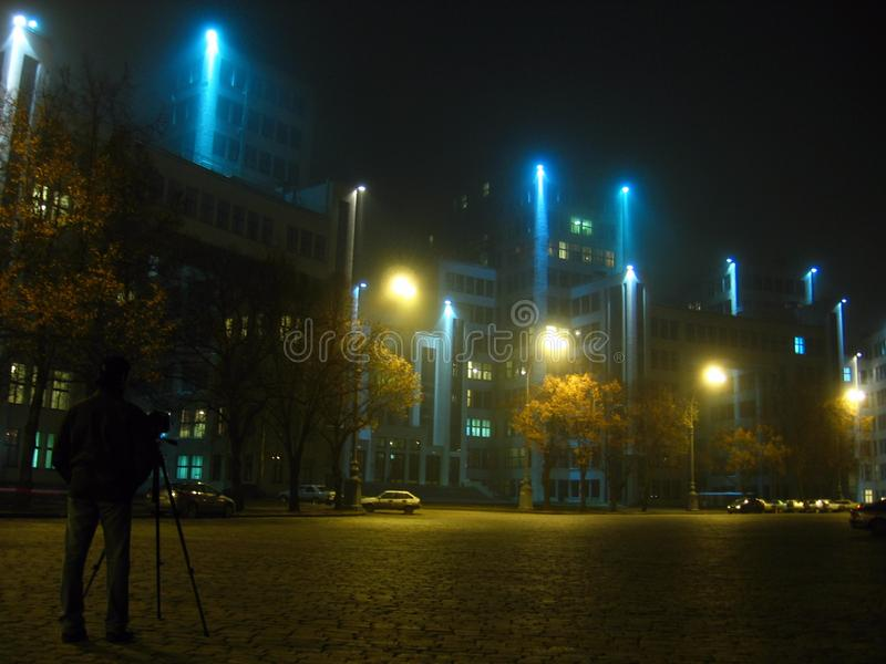 摄影师在晚上拍历史Derzhprom大厦的照片在哈尔科夫,乌克兰 免版税库存图片
