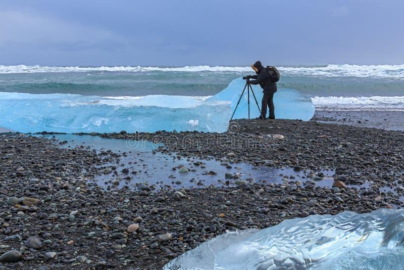 摄影师在Jokulsarlon冰川盐水湖,南冰岛 库存照片