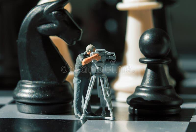 摄影师微型玩偶和棋形象在船上 摄制将死比赛 库存照片