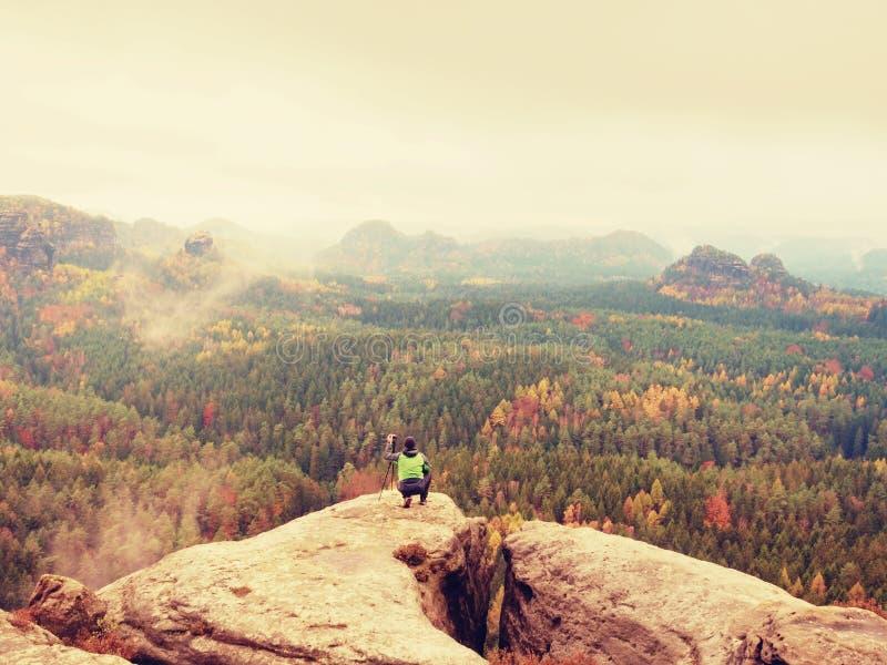 摄影师拍春天自然的照片从锋利的岩石的 高尔夫球外套的远足者和在三脚架的照相机呆在一起 免版税库存照片