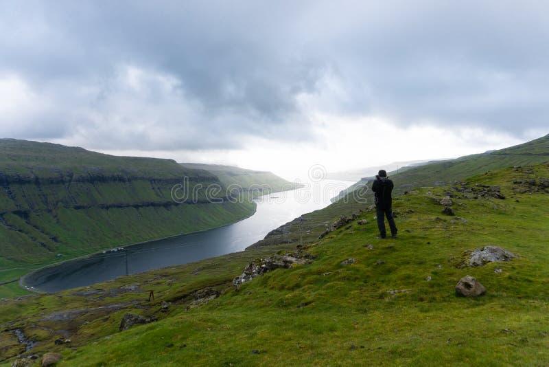 摄影师拍kaldbaksfjordur峡湾照片从小山的 免版税库存图片