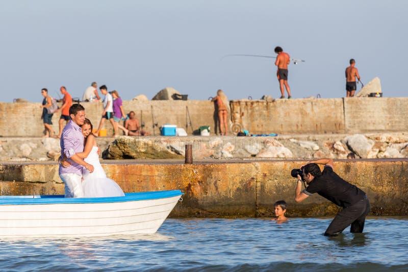 摄影师没膝在水中射击一条小船的两三个富感情的新婚佳偶在黑海海湾,男孩注视 库存照片