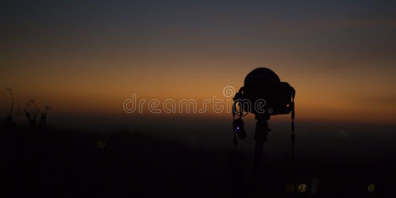 摄影师照相机和橙色天际在黄昏 免版税库存图片