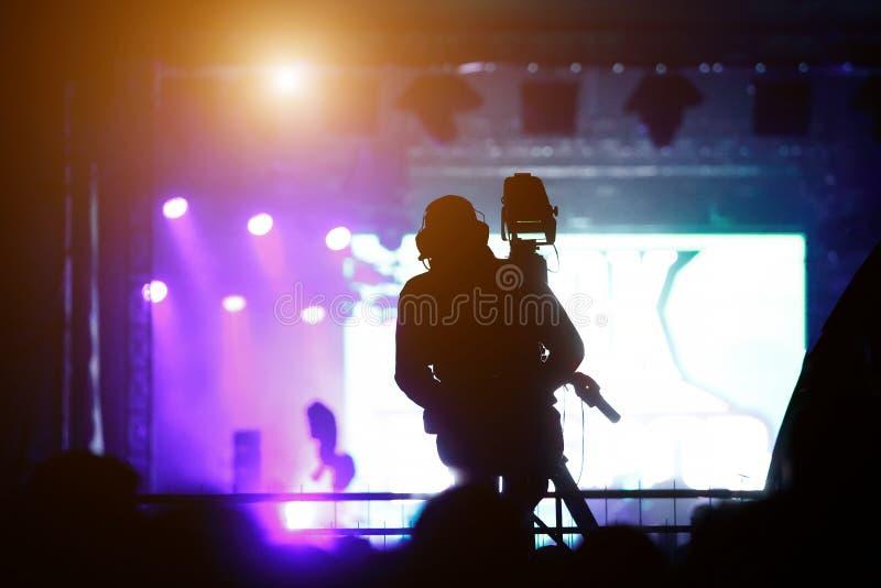 摄影师运作的音乐会的剪影 免版税库存照片