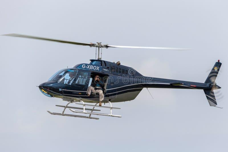 摄影师G-XBOX使用的响铃206B-3直升机拍空中照片 免版税库存图片