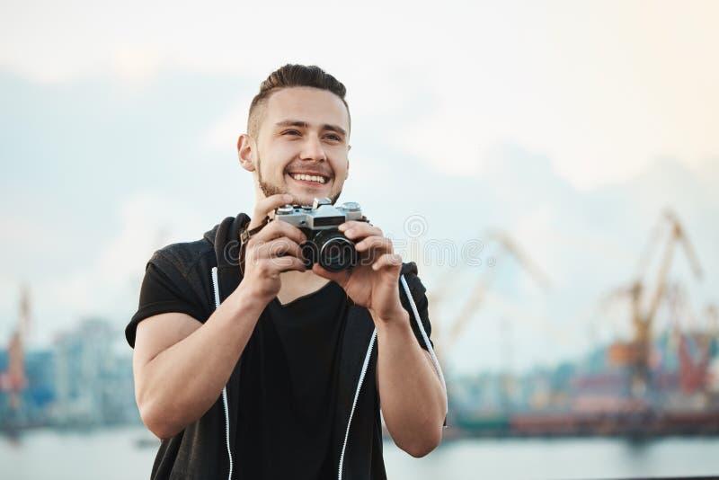 摄影记者喜欢他的工作 广泛地微笑愉快的喜悦的英俊的摄影师画象,当看在旁边和时 免版税库存照片
