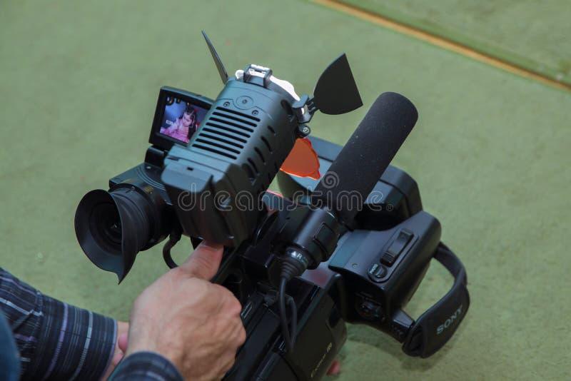 摄象机操作员与他的设备一起使用 工作他的设备录影,照相机,媒介的摄象机操作员 库存照片