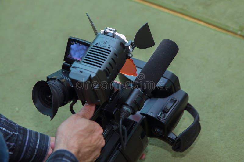 摄象机操作员与他的设备一起使用 工作他的设备录影,照相机,媒介的摄象机操作员 免版税库存照片