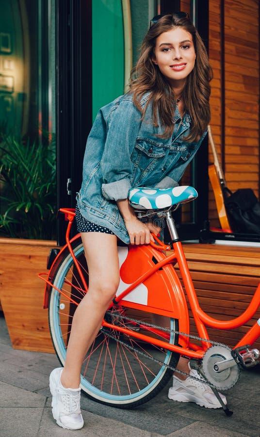 摆在一个夏天室外咖啡馆的背景的时兴的牛仔布夹克的一个极好的东西女孩在一个温暖的晚上 免版税库存图片