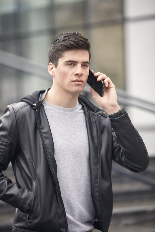 摆在一个年轻英俊的人户外,佩带的夹克,谈话在智能手机 免版税库存图片
