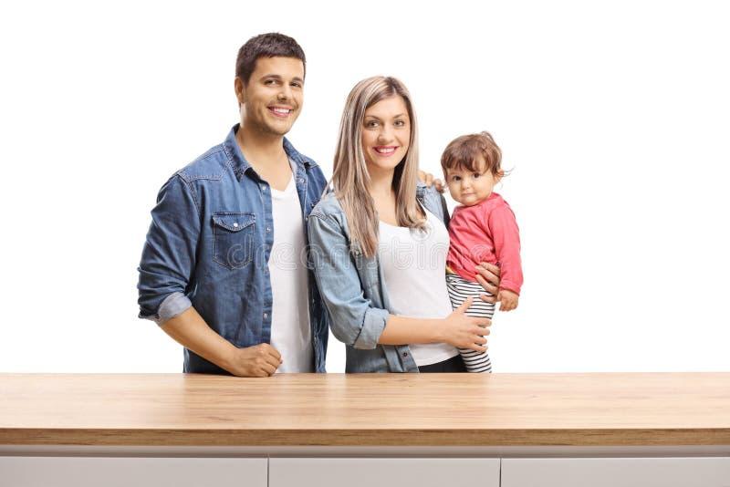 摆在一个木柜台后的母亲、父亲和女婴的年轻家庭 免版税图库摄影