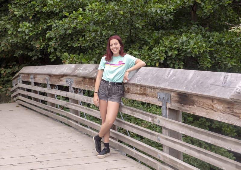 摆在一个木桥的十七岁的熟悉内情的青少年在华盛顿公园树木园,西雅图,华盛顿 库存照片