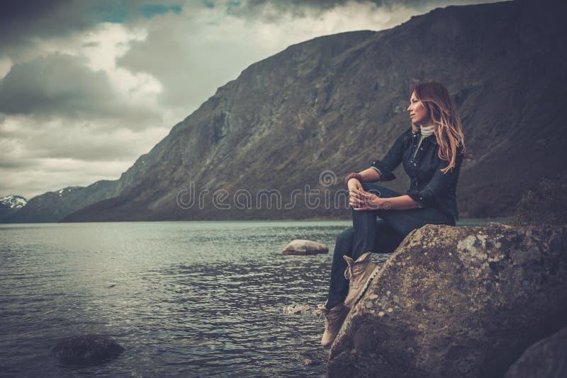 摆在一个狂放的湖的岸的美丽的妇女,有在背景的山的 图库摄影