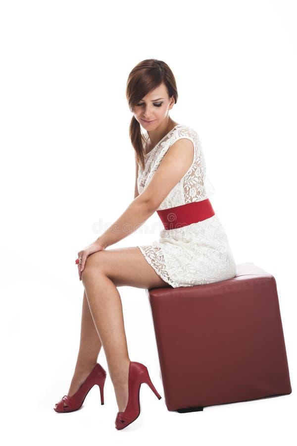 摆在一个皮革位子的端庄的妇女 免版税图库摄影