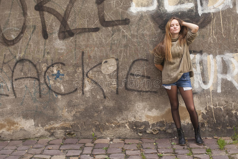 摆在一个石墙附近的女孩在老镇 免版税库存照片