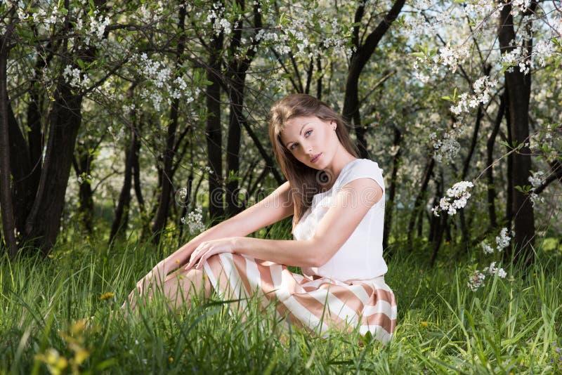 摆在一个花园里的美丽的少妇坐草 免版税库存照片