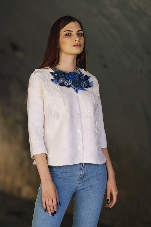 摆在一件白色夹克的时髦的美丽的女孩 免版税库存照片