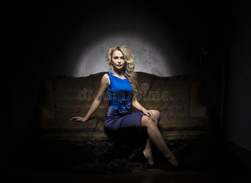 摆在一件蓝色礼服的美丽的白肤金发的妇女 女孩坐沙发 免版税库存图片