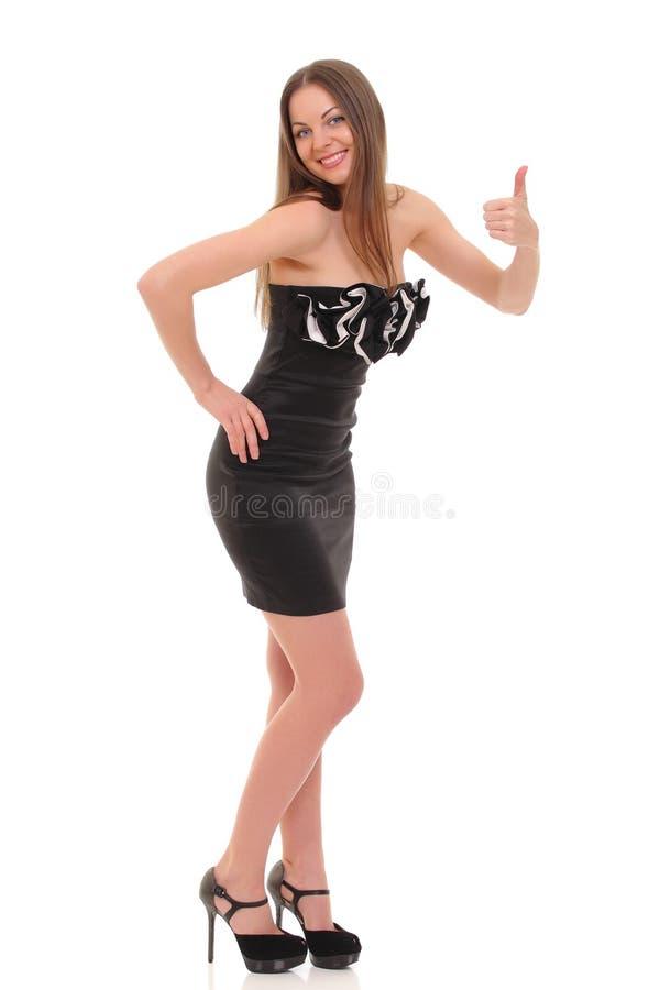 摆在一件黑礼服的女孩被隔绝在白色背景 库存照片