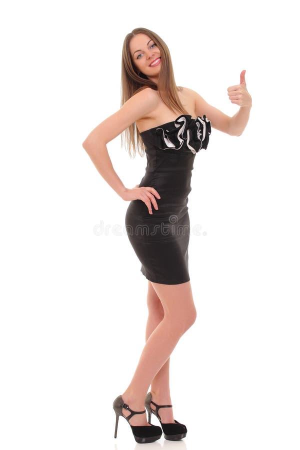 摆在一件黑礼服的女孩被隔绝在白色背景 免版税库存照片