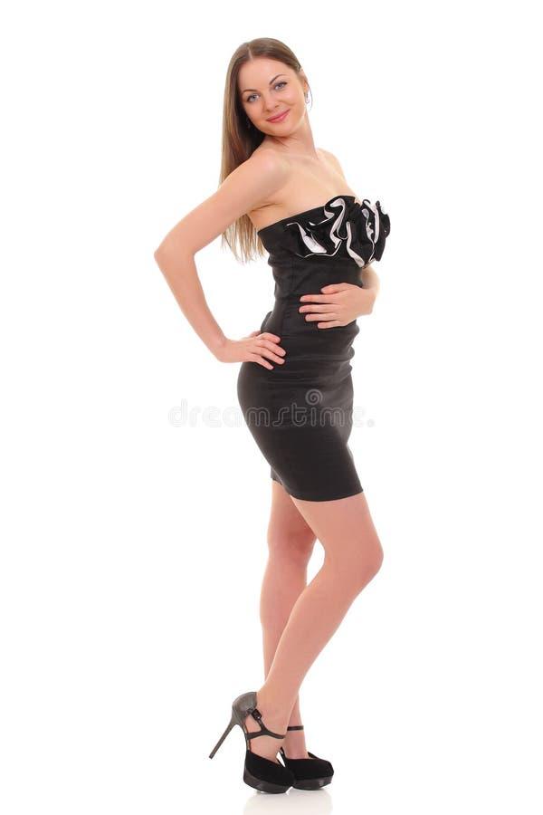 摆在一件黑礼服的女孩被隔绝在白色背景 库存图片