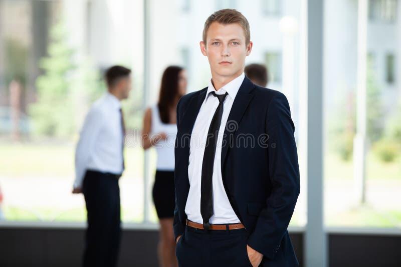 摆在一会儿同事的微笑的商人一起谈话在办公室 库存图片