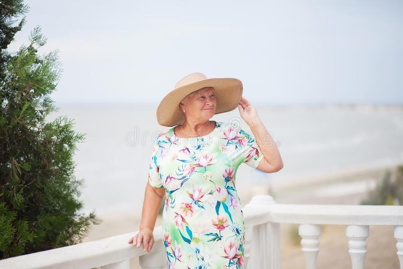 摆在一名年长的妇女,背景的海 免版税图库摄影