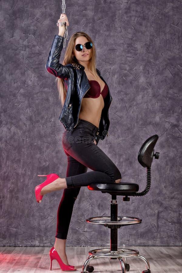黑摆在一张高脚椅子的皮夹克和牛仔裤的美丽的都市时髦女孩 库存图片