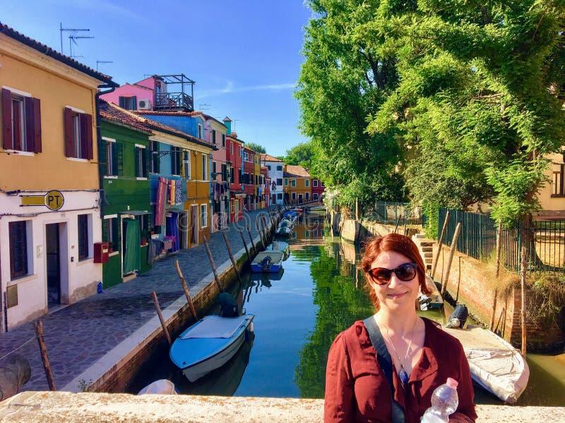 摆在一张Burano,意大利照片与老五颜六色的历史的家和运河的一座桥梁的一个俏丽的年轻女性游人  免版税库存照片