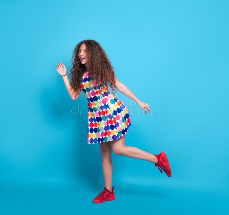 摆在一条腿的有波浪头发的女孩 免版税库存图片