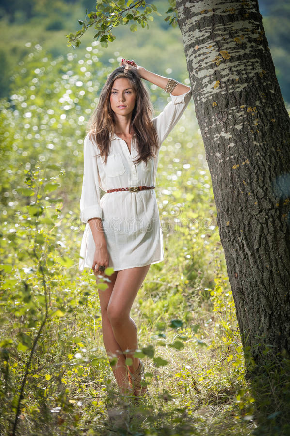 摆在一棵树附近的白色短的礼服的可爱的少妇在一个晴朗的夏日 美好的享用的女孩本质 图库摄影