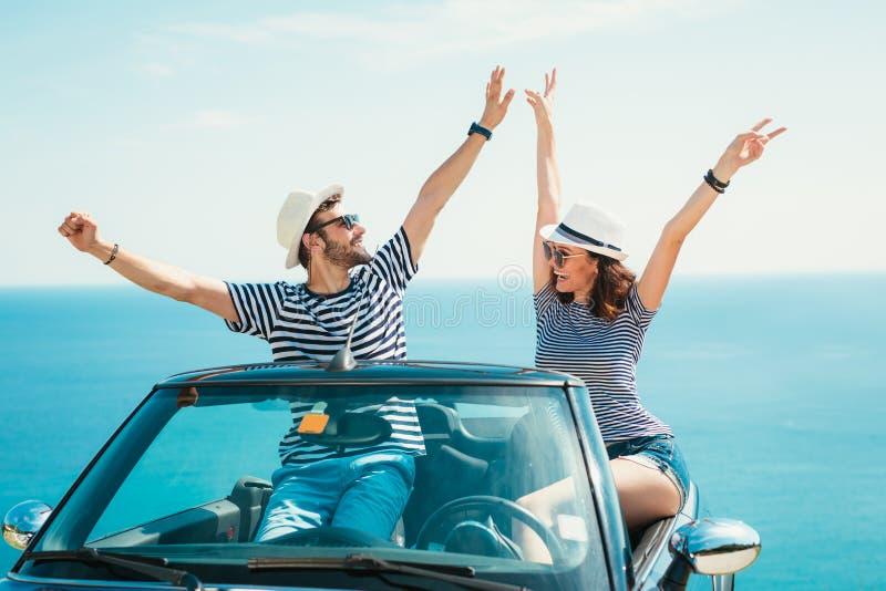 摆在一辆敞篷车汽车的年轻有吸引力的夫妇 免版税库存照片