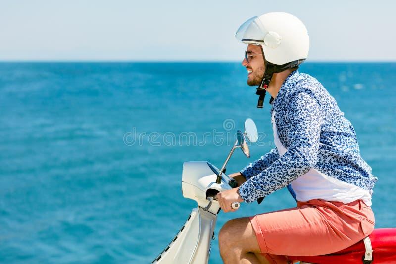 摆在一辆滑行车的英俊的人在假期上下文 街道时尚和样式 库存图片