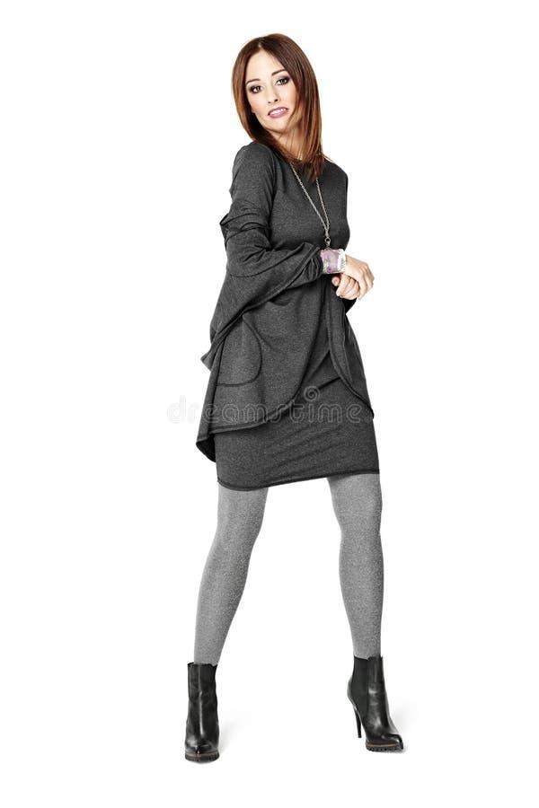 摆在一件灰色礼服的妇女 免版税库存图片
