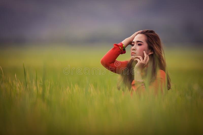 摆在一件红色礼服的越南年轻美丽的浅黑肤色的男人 免版税库存图片