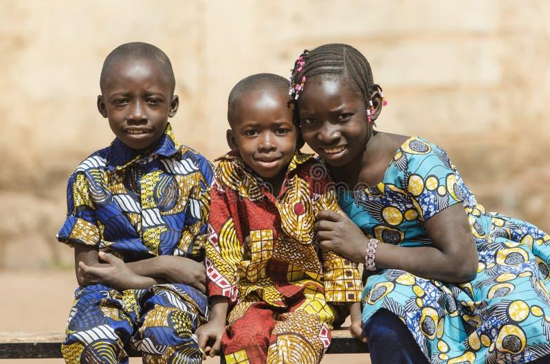 摆在三个华美的非洲黑人种族的孩子户外 库存图片