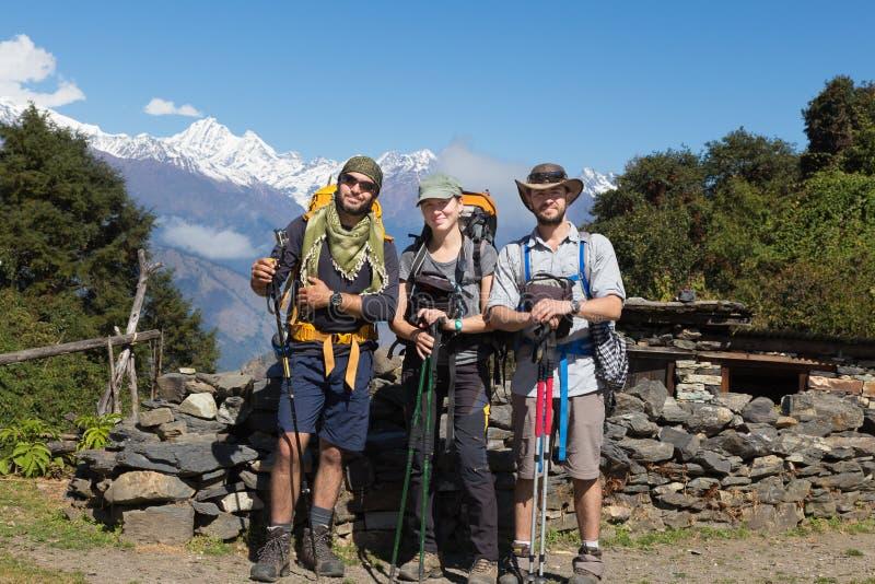 摆在三个背包徒步旅行者的游人,雪山峰土坎 免版税库存图片