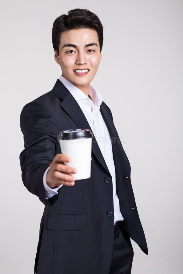 摆在与一个一次性咖啡杯的一个亚裔商人的演播室画象 免版税库存照片