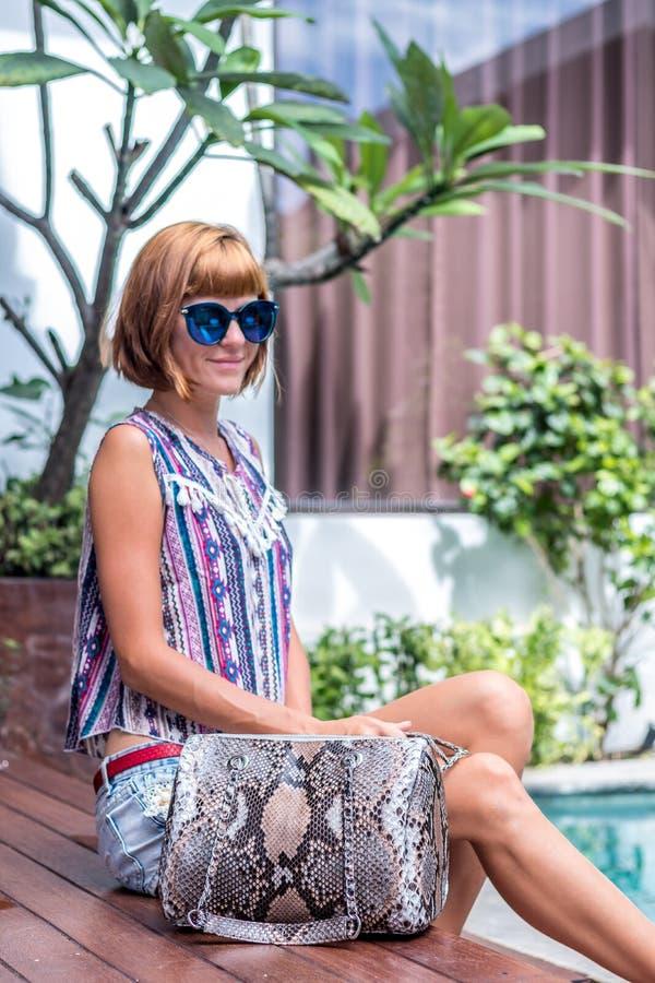 摆在与一个大超级时兴的snakeskin Python提包的游泳池附近的女孩 热带海岛巴厘岛 免版税库存照片