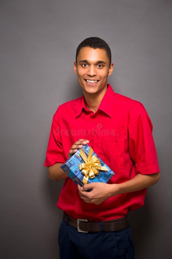 摆在与一个礼物的英俊的年轻人在演播室 免版税库存照片